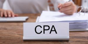 CPA name plate on the desk and a woman working on the backdrop