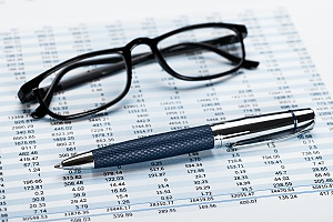 accountant financial records shown with glasses and a pen