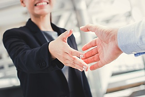 a CPA shaking hands with a business owner after government contract proposal