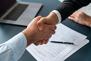 a CPA shaking hands with a business owner after working on government contract bidding