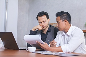 a business owner discussing government contract termination with a consultant