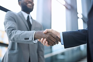 a certified public accountant shaking hands with a business owner after a financial reporting presentation