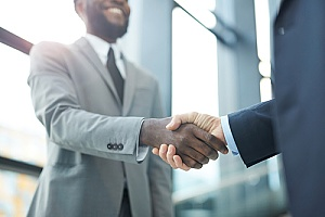 a government contractor shaking hands with an accountant after getting a contract modification approved