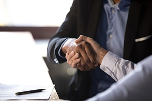 a CPA shaking hands with a business owner after preparing taxes