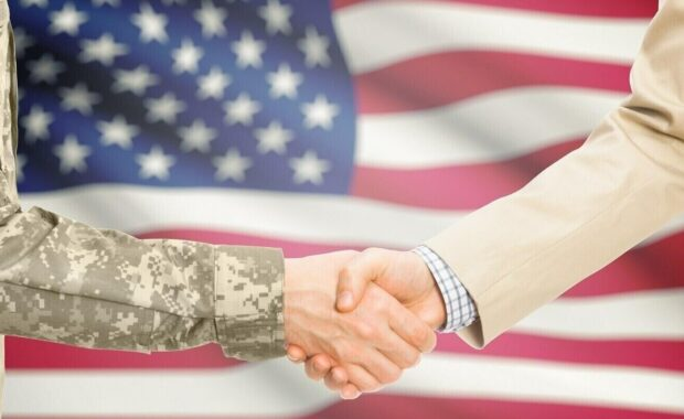 dcaa compliance- american soldier and civil man in suit shaking hands with us flag on background