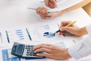 businesswoman holding a pen pointing the graph with partnership to analyze the marketing plan