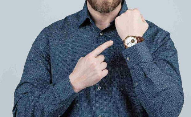 a man pointing at his watch representing DCAA compliant timekeeping