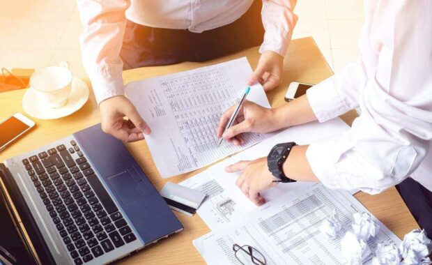 business people hands writing accounts payable document while discussing