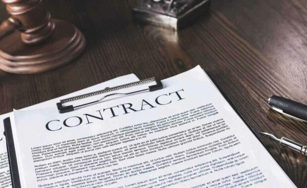 juridical contract on wooden table with pen and hammer, law concept