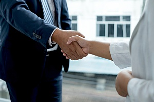 two business owners shaking hands after a successful merger