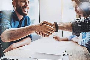a business owner shaking hands with an outsourced accountant who is assisting with payroll