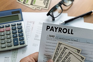 a form 1040 and cash representing payroll