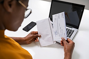 an employee receiving a paycheck due to the help of payroll services