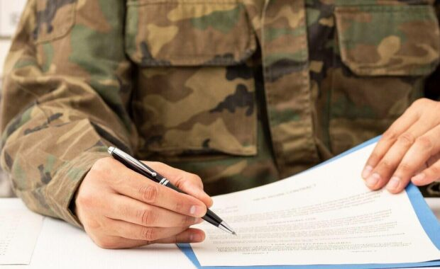 executive military man hands signing contract on a desk at work