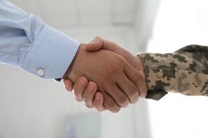 soldier and businessman shaking hands indoors