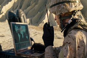 soldier is using laptop computer and radio for communication during military operation
