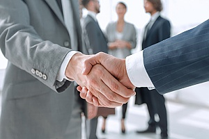 a professional CPA shaking hands with a government contractor after a successful REA