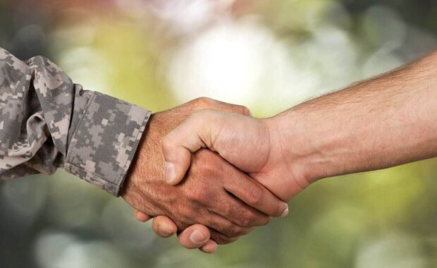 man shaking hand with military person
