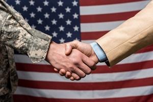 selective focus military men shaking hands near american flag