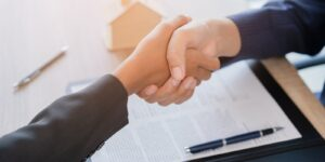 agent shake hands after customer signing contract